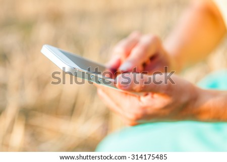 Beautiful young woman photographing herself with phone.