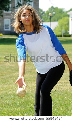 Beautiful young woman pitching softball - stock photo