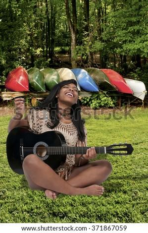 Beautiful young woman playing an acoustic guitar - stock photo