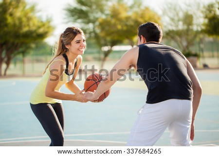 Beautiful young woman playing basketball with her boyfriend on a court outdoors and having some fun - stock photo