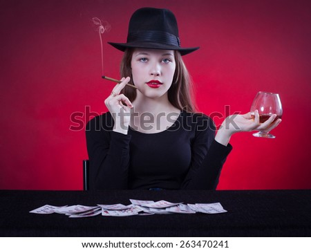 Beautiful young woman playing cards sitting at the table and smoking a cigar. - stock photo