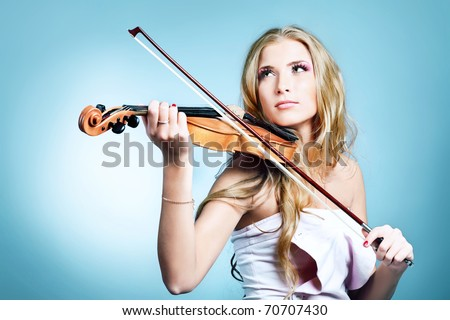 Beautiful young woman playing her violin with expression. Over grey bakground.