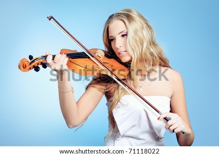 Beautiful young woman playing her violin with expression. Over grey bakground. - stock photo