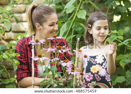 Beautiful young woman playing in garden with her little sister.