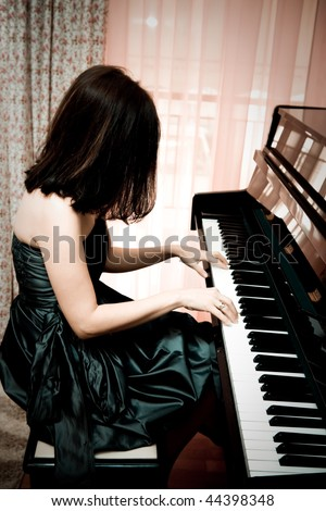 Beautiful young woman playing piano, vintage portrait - stock photo