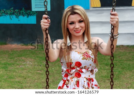 Beautiful Young Woman Playing Swing In The Park Playground - stock photo