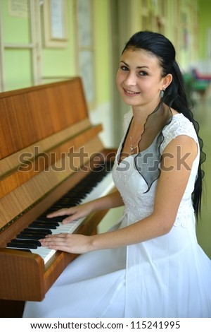 beautiful young woman playing the piano - stock photo