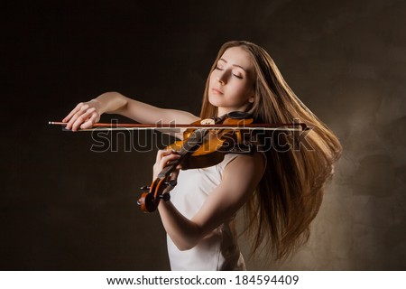 Beautiful young woman playing violin over black background - stock photo