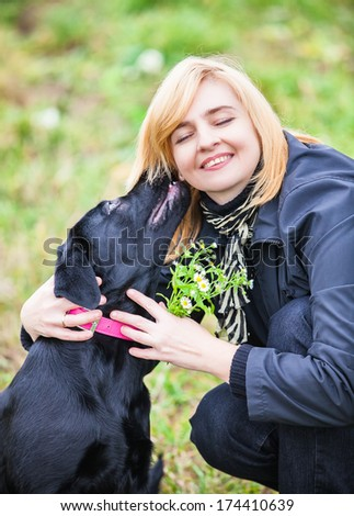 beautiful young woman playing with dog - stock photo