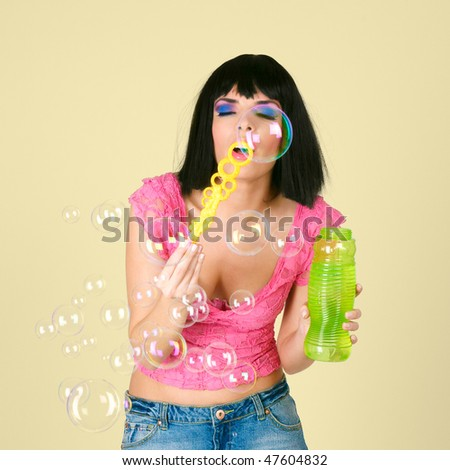 Beautiful young woman playing with soap bubbles - stock photo