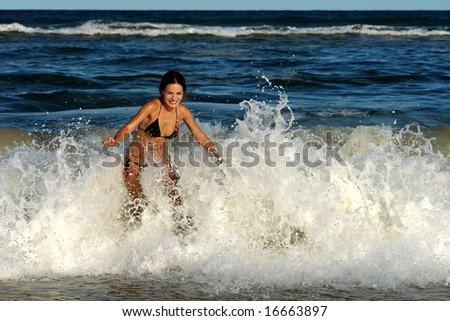 Beautiful young woman playing with waves on the ocean beach