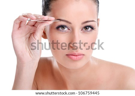 Beautiful young woman plucking eyebrows, looking at camera as mirror - stock photo