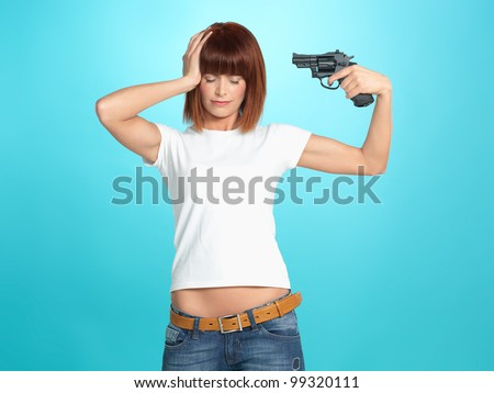 beautiful, young woman pointing a gun at her head, on blue background - stock photo