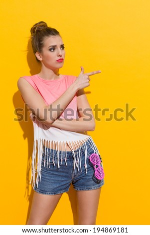 Beautiful young woman pointing and looking away. Three quarter length studio shot on yellow background. - stock photo