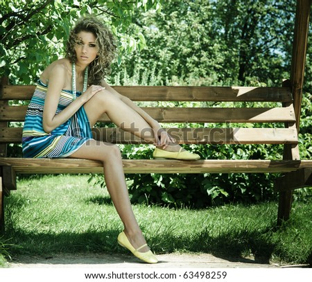 Beautiful young woman portrait on bench in park - stock photo