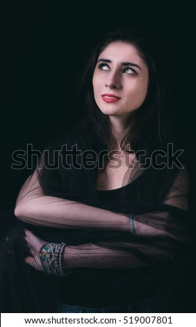 Beautiful young woman portrait on dark background in low key technique