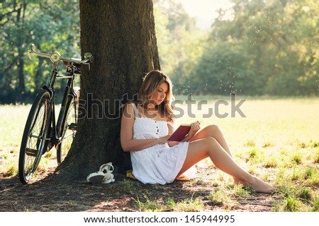 Beautiful young woman portrait reading a book under a tree with bicycle in the park.  - stock photo