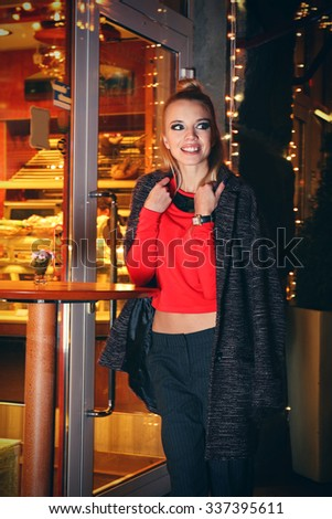 Beautiful young woman poses near bright cafe on the street at night
