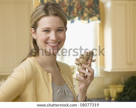 Beautiful young woman poses with a piece of ginseng while standing in the kitchen.  Horizontal shot. - stock photo