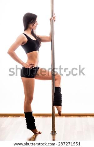 Beautiful young woman posing at pole - stock photo