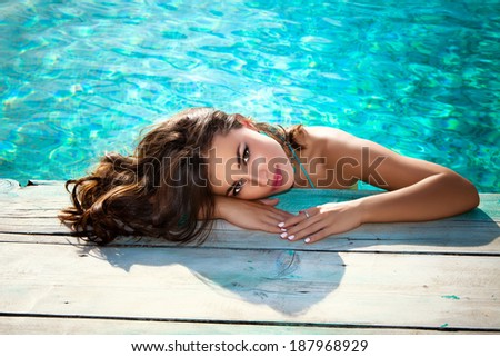 beautiful young woman posing by the pool, summer day, outdoor - stock photo