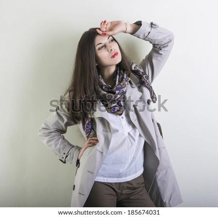 Beautiful young woman posing in a light raincoat. - stock photo