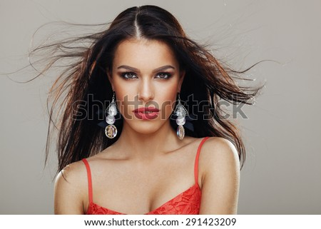 Beautiful young woman posing in a studio with flying hair