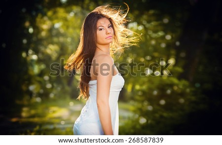 Beautiful young woman posing in a summer meadow. Portrait of attractive brunette girl with long hair relaxing in nature, outdoor shot in sunny day. Lady in white enjoying the nature, harmony concept - stock photo