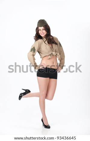 Beautiful young woman posing in black shorts, black heels and a military shirt and cap on a white background. - stock photo