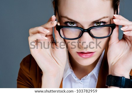 Beautiful young woman posing in business suit and glasses. - stock photo