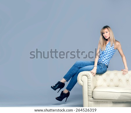 Beautiful young woman posing in fashionable jeans, looking at camera. Blonde girl. Studio photo. - stock photo
