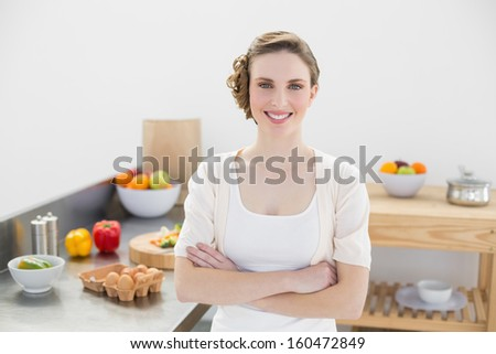 Beautiful young woman posing in her kitchen with arms crossed smiling at camera - stock photo