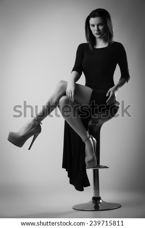 Beautiful Young Woman Posing in Long Black Dress Sitting on a Bar Stool - stock photo