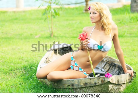 Beautiful young woman posing in old wooden boat - stock photo