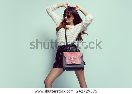 beautiful young woman posing in sunglasses, leather shorts, handbag and sweater. Fashion clothes - stock photo