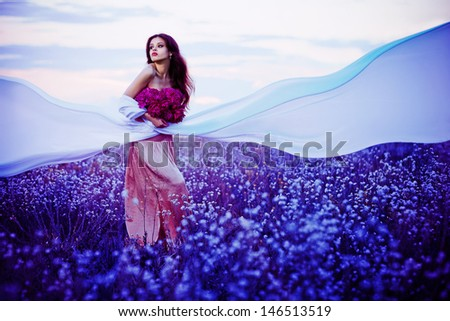 Beautiful young woman posing in the sunset field with flowers and white fabric - stock photo
