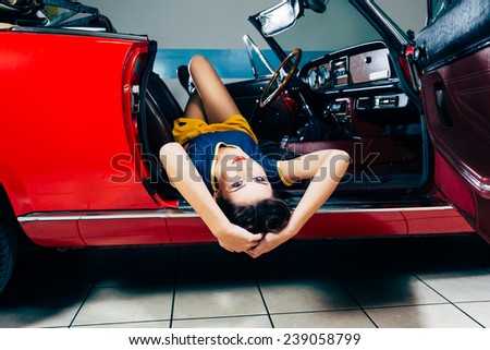 Beautiful young woman posing in vintage car  - stock photo