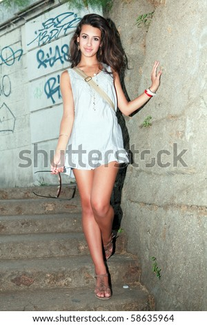 Beautiful young woman posing on the steps leading to the Sacre-Coeur Basilica in Montmartre in Paris, France. - stock photo