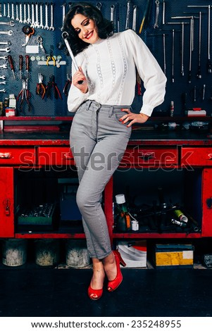 Beautiful young woman posing on vintage car shop bench - stock photo