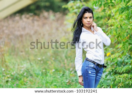Beautiful young woman posing outdoors - stock photo
