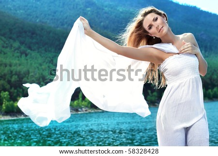 Beautiful young woman posing over sea and mountains.