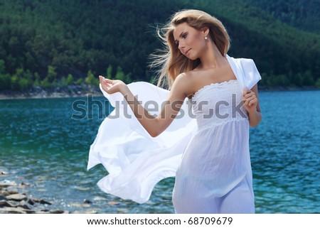 Beautiful young woman posing over sea beach. - stock photo