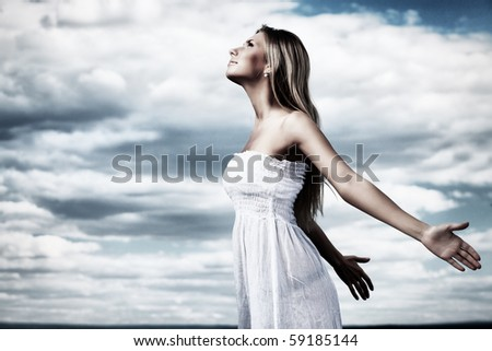 Beautiful young woman posing over summer sky. - stock photo