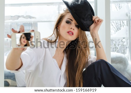 Beautiful young woman posing taking selfshot or selfy picture of herself on mobile device portrait - stock photo
