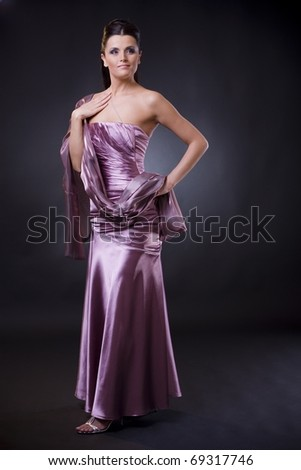 Beautiful young woman posing, wearing a light purple evening dress with stole.? - stock photo
