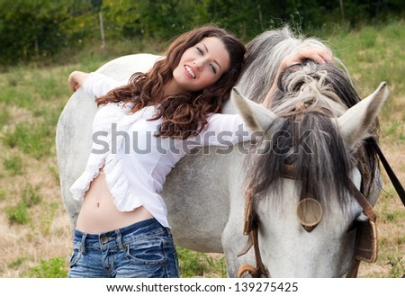 Beautiful young woman posing with a farm horse - stock photo