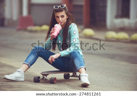Beautiful young woman posing with a skateboard seat on skate, street fashion lifestyle. Keep cocktail in hand. - stock photo