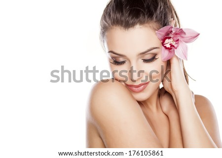 beautiful young woman posing with orchid - stock photo