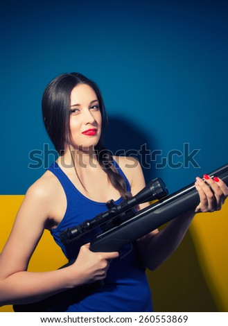 beautiful young woman posing with rifle against blue and yellow background - stock photo