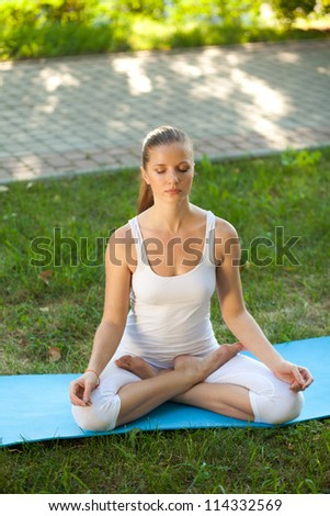Beautiful young woman practices yoga in nature. Lotus Pose, eyes closed - stock photo